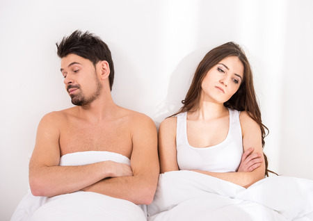 arguing: Top view of young couple under the covers in bed turned away from each other.