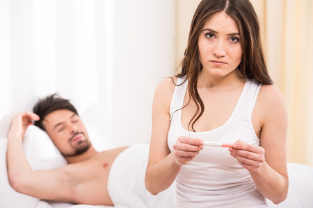 Upset woman is looking in pregnancy test with her sleeping husband  photo