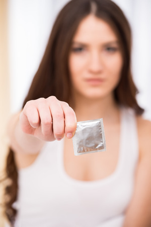 Young woman is holding a condom. Focus on a condom.