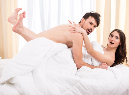 anxious: Young love couple in bed, romantic scene in bedroom.