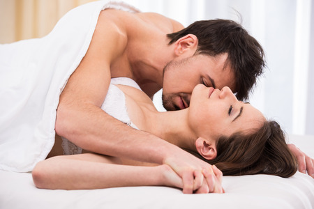 man looking out: Young love couple in bed, romantic scene in bedroom.