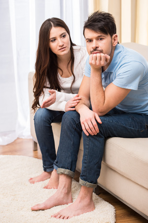 angry women: Portrait of frustrated couple are sitting on couch and are quarreling with each other. Stock Photo