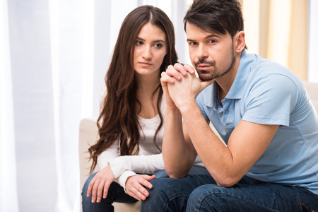 Portrait of frustrated couple are sitting on couch and are quarreling with each other. Stock Photo