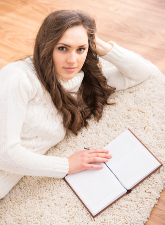 Top view of young woman with a book is lying on the floor. photo