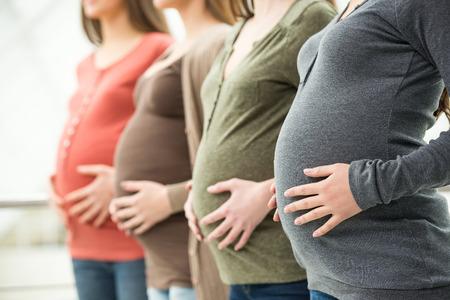 Vista lateral de tres mujeres embarazadas están tocando su vientre con las manos. Concepto de la maternidad.