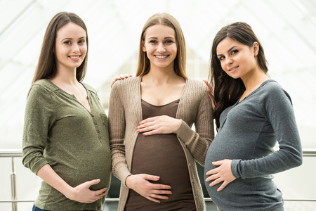 Maternity concept. Portrait of three happy pregnant women. Stock Photo