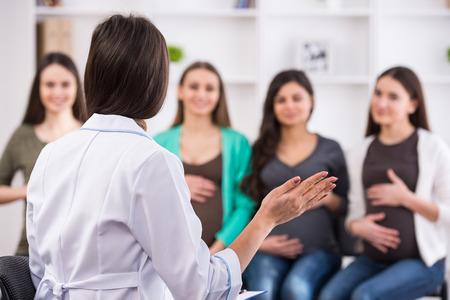 clase media: Las mujeres embarazadas están escuchando al doctor en clase prenatal en el hospital