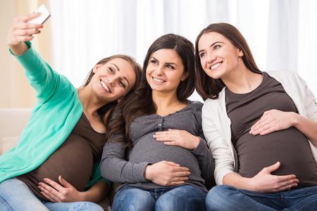 Three happy pregnant women are making selfie photo. photo