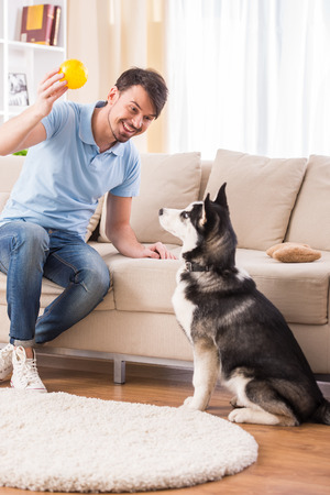 single rooms: Happy man is playing with his dog at home.