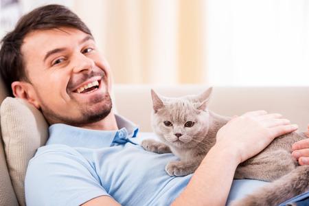 kotów: Uśmiechnięty młody człowiek z jego cute kot na kanapie w domu.