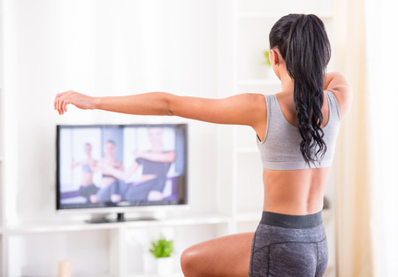 Rear view of a young woman doing home exercises while watching program on television photo