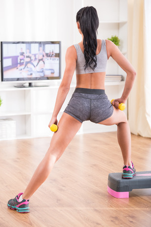 Woman is doing fitness at home on her living room floor while watching and participating in a class photo