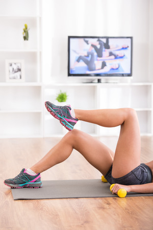 Woman is doing fitness at home on her living room floor while watching and participating in a class. Close-up of legs. photo