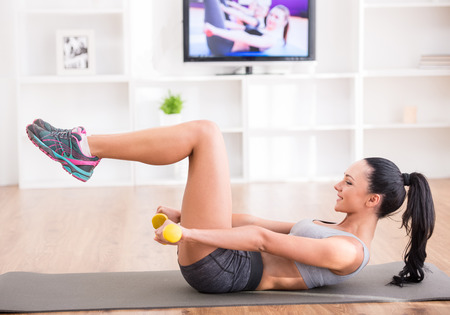 Woman is doing fitness at home on her living room floor while watching and participating in a class. photo