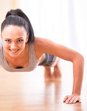 Fitness, sport, training and lifestyle concept.  Smiling woman is doing exercises at home. photo