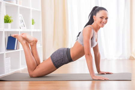 Pretty woman is doing fitness at home on her living room floor. Fitness, workout, healthy living and diet concept. photo
