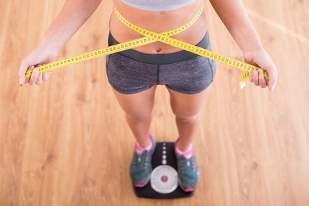 losing weight: Top view of pretty slim woman with measure around her body is standing on the scales.