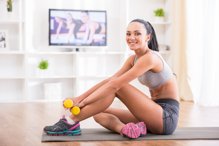 Fitness at home concept. Smiling young woman is sitting on mat with sports equipment at home. photo