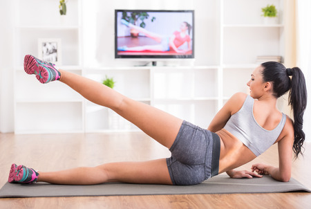 Fitness, workout, healthy living and diet concept.  Rear view of young woman is stretching on floor and watching tv at home. photo