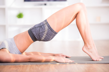 Pretty woman is doing fitness at home on her living room floor. photo