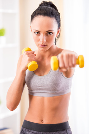 Young woman is exercising with dumbbells at home. Fitness, workout, healthy living and diet concept. photo