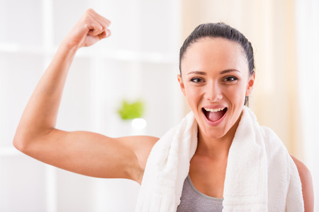 Close-up of young sporty woman flexing her biceps. photo