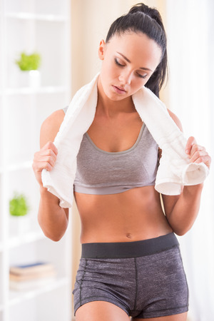 Young tired woman after fitness exercise with towel. photo