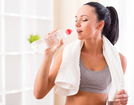 Fitness, home and diet concept. Smiling young woman with bottle of water after exercising at home. photo