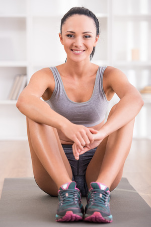 Fitness at home concept. Smiling young woman is sitting on mat at home. photo