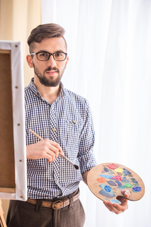 Young male artist is drawing on an easel and holding palette in hand. photo