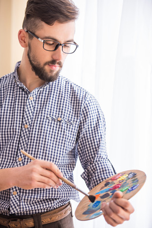 Portrait of a young male artist is holding a brush and mix color oil painting on palette. photo