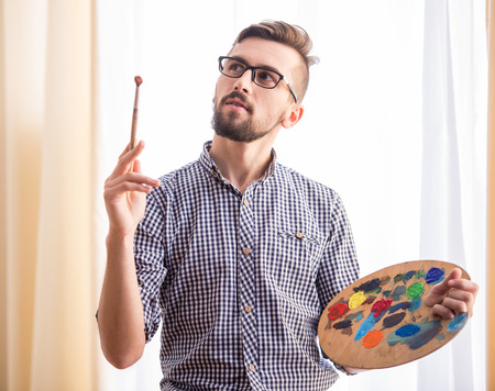 artistas: Retrato de un artista masculino joven est� sosteniendo un pincel y mezclar la pintura al �leo de color en la paleta.
