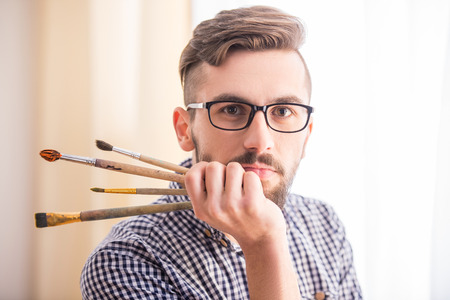 male: Portrait of a young male artist with brushes for painting.