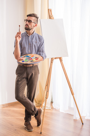 Portrait of highly gifted painter is holding brush in his hand is going to paint a picture.