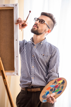 Portrait of highly gifted painter is holding brush and palette in his hand is finishing his picture. photo
