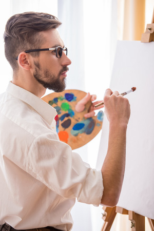 Side view of young artist  with brush and palette is going to painting a picture. photo