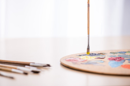 Close-up image of brushes, paints and palette on the table. Stok Fotoğraf