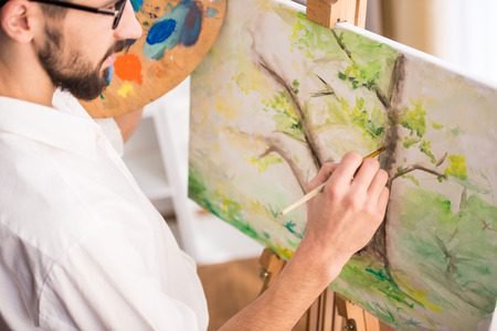 Top view of highly gifted painter while he is painting his picture. Close-up. Stock Photo