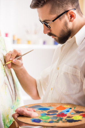 gifted: Portrait of highly gifted painter is holding brush and palette in his hand is finishing his picture.