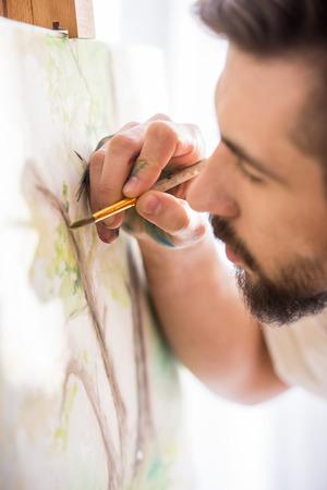 pintor: Altamente pintor dotado es la celebraci�n de pincel y la paleta en la mano est� terminando su imagen. De cerca. Foto de archivo