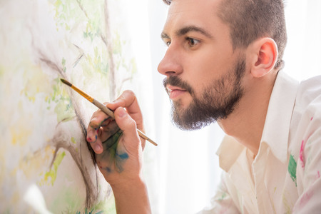 gifted: Highly gifted painter is painting his picture with brush and palette. Close-up.