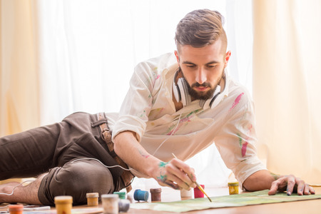 artistic: Young artist is painting on canvas is lying on studio floor while listening a music. Stock Photo