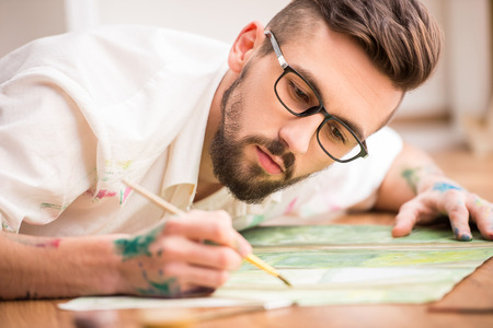 artist painting: Young artist is painting on canvas is lying on studio floor. Close-up. Stock Photo