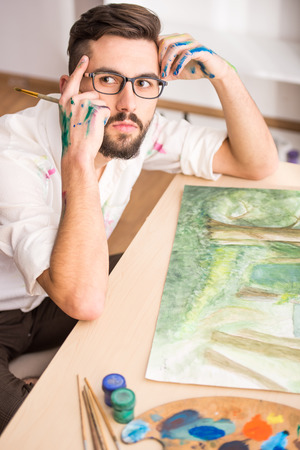 gifted: Side view of highly gifted painter while he is painting his picture. Stock Photo