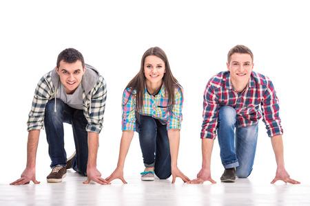 Mensen op startlijn. Groep jonge mensen staan op de startlijn en kijken terwijl geïsoleerd op wit. Stockfoto