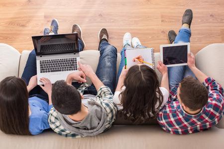 Vue de dessus d'un quatre jeunes, des étudiants sont assis sur le canapé avec un ordinateur portable et une tablette, étudient. Banque d'images - 36179826