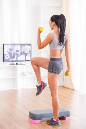 Young woman is exercising with dumbbells and step at home. photo