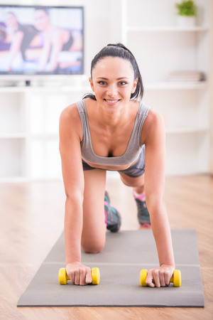 Woman is doing fitness at home on her living room floor while watching and participating in a class. She is looking at the camera. photo