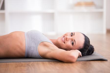 haciendo ejercicio: Primer plano de mujer joven y deportivo est� mintiendo en la estera en casa. Foto de archivo