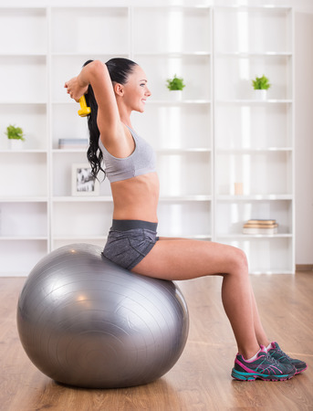 Fitness, sport, training and lifestyle concept. Pretty woman with exercise ball at home. photo